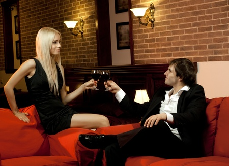 couple couch: romantic evening date in hotel room,  happy couple with wine glass sit on red sofa