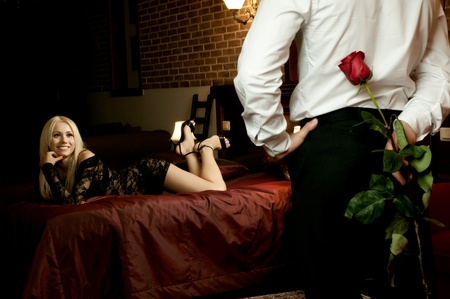 romantic sexy couple: romantic evening date in hotel room, guy with red rose and sexy girl,  in bedroom Stock Photo