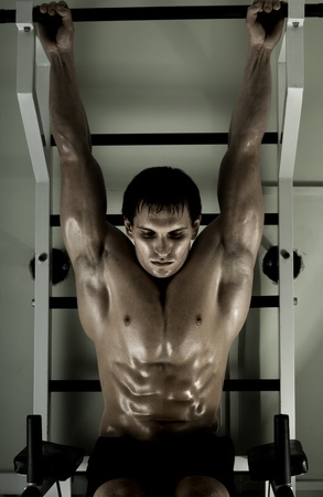 very power athletic guy ,  execute exercise tightening  on horizontal bar, in  sport-hall, hard light Stock Photo - 12228954