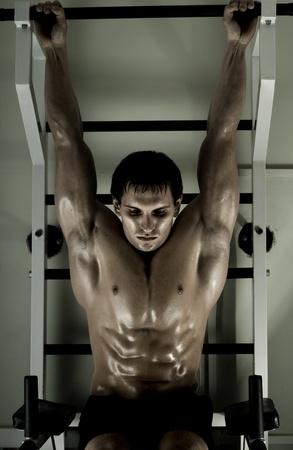 rekstok: zeer macht atletische jongen, uitvoeren oefening aanscherping op rekstok, in sport-hall, hard licht Stockfoto