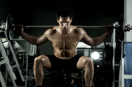 very power athletic guy ,  execute exercise with  dumbbells, in  sport-hall Stock Photo