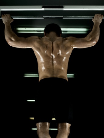 very power athletic guy ,  execute exercise tightening  on horizontal bar, in  sport-hall, glamour light Stock Photo - 12228930