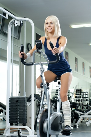 physical fitness: happy cutie athletic girl ,  execute exercise on exercise bicycle  and smile, in  sport-hall