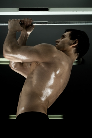 very power athletic guy ,  execute exercise tightening  on horizontal bar, in  sport-hall, glamour light Stock Photo - 12228934