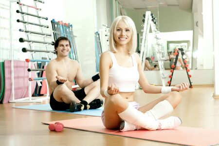 happy cutie athletic girl and guy,  execute exercise in pose lotus and smile, in  sport-hall photo