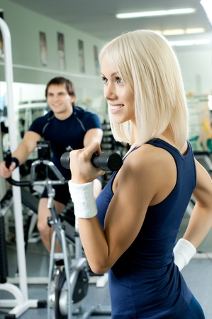 sports hall: happy cutie athletic girl ,  exercise with dumbbells and smile, in  sport-hall