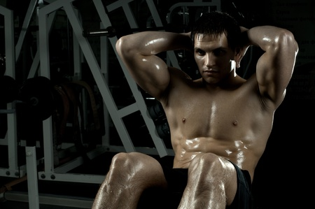 powerful man: very power athletic guy ,  execute exercise on muscles belly, in  sport-hall, beauty glamour light Stock Photo