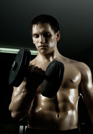 very power athletic guy ,  execute exercise with  dumbbells, in  sport-hall, beauty glamour light Stock Photo - 12229007