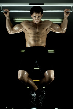very power athletic guy ,  execute exercise tightening  on horizontal bar, in  sport-hall, glamour light Stock Photo - 12228929