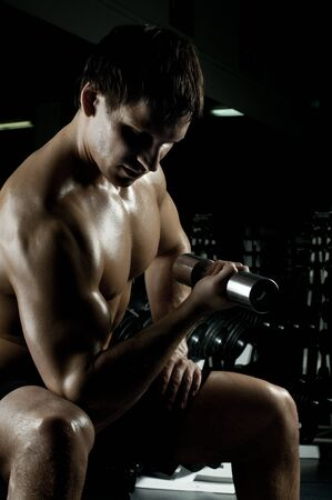 very power athletic guy ,  execute exercise with  dumbbells, in  dark sport-hall Stock Photo - 12229068