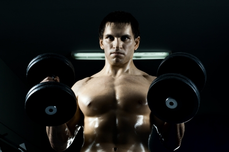tough man: very power athletic guy ,  execute exercise with  dumbbells, in  dark sport-hall