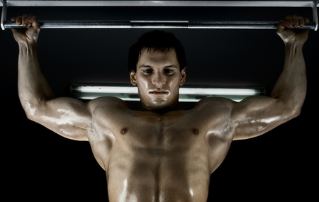 very power athletic guy ,  execute exercise tightening  on horizontal bar, in  dark sport-hal Stock Photo - 12229054