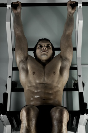 very power athletic guy ,  execute exercise tightening  on horizontal bar, in  sport-hall, hard light Stock Photo - 12229053