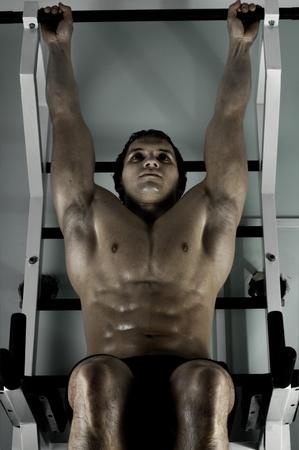 rekstok: zeer krachtige atletische man, uit te voeren uit te oefenen vast op horizontale balk, in de sport-hal, hard licht Stockfoto