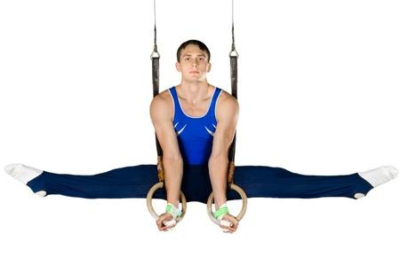 El deportista del hombre, lleva a cabo ejercicio difícil, gimnasia deportiva, en el fondo blanco, aislados Foto de archivo