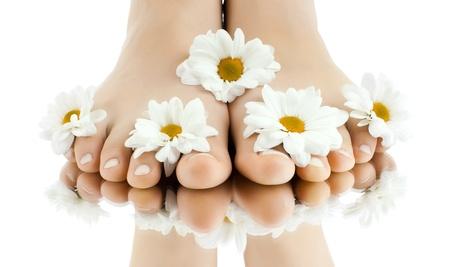 pies bonitos: las lindas piernas femeninas con fowers, sobre fondo blanco, aislado, de cerca