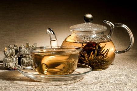 glasswork: the glass teapot and cup with green tea, on flax-fibre