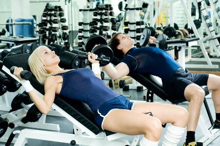 happy cutie athletic girl and guy,  lie exercise with dumbbells and smile, in  sport-hall photo