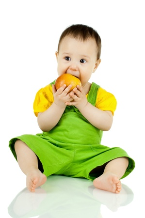 gaily: the little baby in green dress, eating apple, sit on white background, isolated Stock Photo