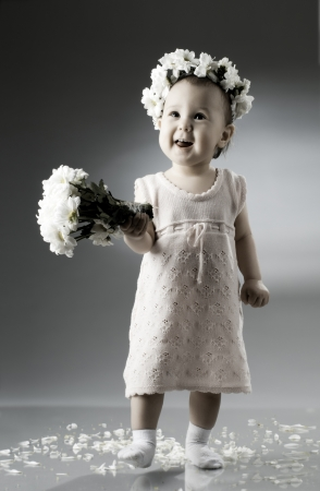 little boy and girl: beautiful  little kid with  bouquet and diadem of flowers , sit and  smile  Stock Photo