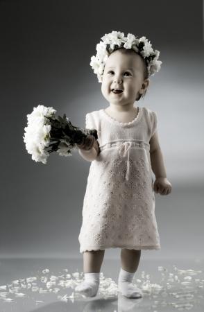 꽃다발과 꽃의 왕관과 함께 아름 다운 작은 아이가 앉아서 미소