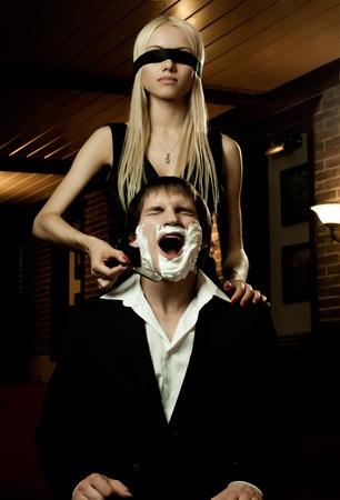 smoothfaced: beautiful youth woman  with blindfold,  get shave guy  hazardous razor Stock Photo