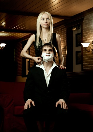 unruffled: beautiful youth woman  with blindfold,  get shave guy  hazardous razor Stock Photo