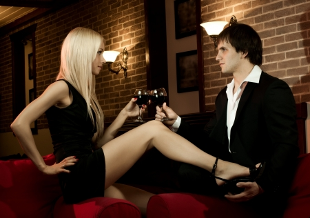 romantic evening with wine: romantic evening date in hotel room,  happy couple with wine glass sit on red sofa