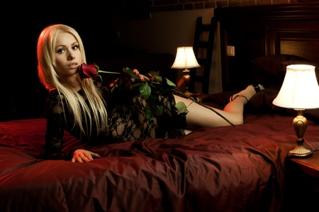 vehement: the beautiful  young woman lie on  bed with rose, in hotel room