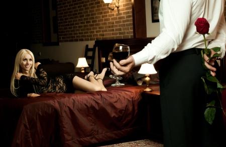couple au lit: date de soir�e romantique en chambre d'h�tel, mec avec la rose rouge, jeune fille sur un lit sourire Banque d'images