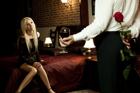 romantic evening date in hotel room, guy with red rose ,  girl on bed smile photo