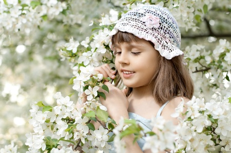 belle: The beautiful little girl, with bush blossoming apple-tree, smiles Stock Photo
