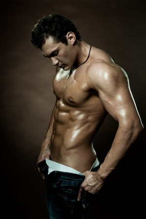 the very muscular handsome sexy guy on dark  brown background Stock Photo - 12466139