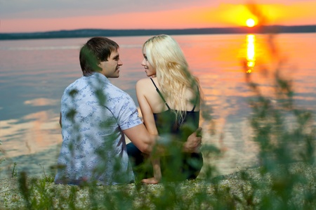 romantic evening date on nature, couple on beautiful sunset or sunrise on shore  lake photo