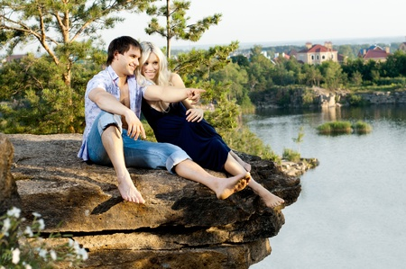 aloft: romantic  date on nature, happy couple sit aloft on rock  with beautiful view
