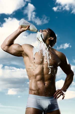 undressed young: the very muscular handsome sexy guy on sky background, drink milk, focus on face