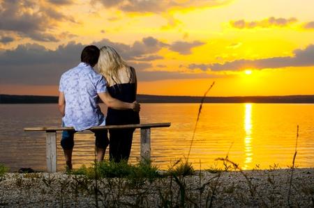 jovenes enamorados: Foto horizontal de la feliz pareja, al aire libre en la salida del sol puesta de sol de belleza o, en la playa Foto de archivo