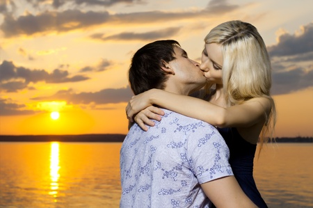 necking: horizontal photo the very happy  sexy pretty couple, kiss, outdoor on sunset or sunrise Stock Photo