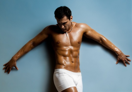 undressed: the very muscular  undressed handsome sexy guy on blue background Stock Photo