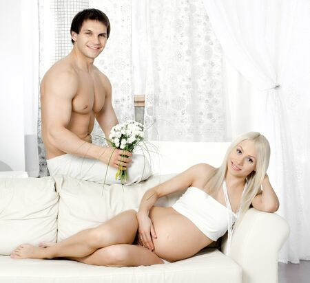 fetation: young pregnant woman with husband  on white sofa in light  home room Stock Photo