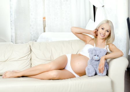 fetation: young pregnant woman lie  on white sofa in light  home room Stock Photo