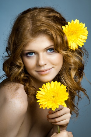 the very  pretty red-haired freckled young woman with yelow flowers on blue background, vertical portrait photo