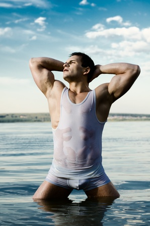 athletic type: the very muscular handsome sexy guy on sky and sea background