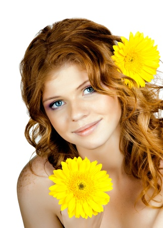 yelow: the very  pretty red-haired freckled young woman with yelow flowers , vertical portrait, isolated Stock Photo