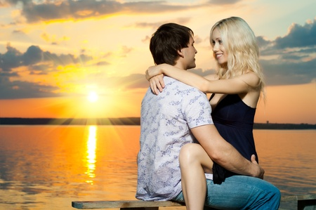 courting: romantic evening date on nature, couple on beautiful sunset or sunrise on shore  lake