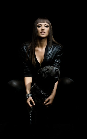female sexy chains: the beautiful  young woman sit with dog on black background
