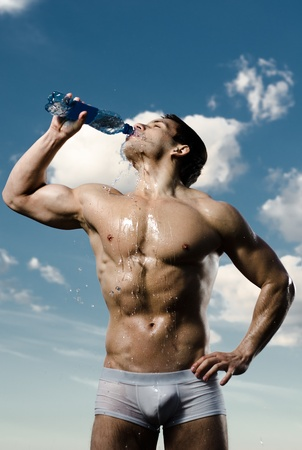athletic type: the very muscular handsome sexy guy on sky background, drink water, focus on face