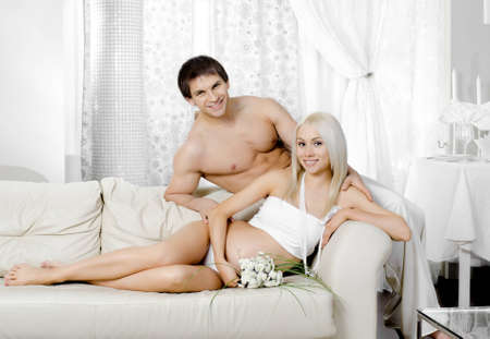 young pregnant woman with husband  on white sofa in light bedroom photo