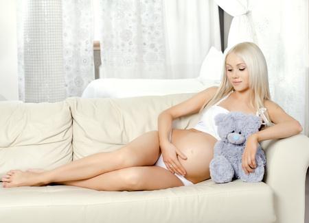pregnant underwear: joven mujer embarazada con flores, se encuentran en la cama en la habitaci�n de la luz blanca