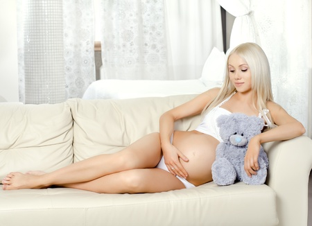 pregnant blonde: young pregnant woman with flowers,  lie  on white bed in  light bedroom